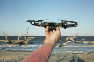 a DJI spark being held up in front of the ocean, facing the camera